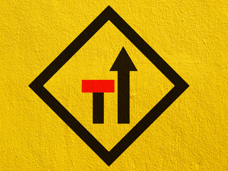 warning road signs painted on a stucco wall outside