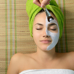 Beautiful young woman having facial mask apply by beautician in