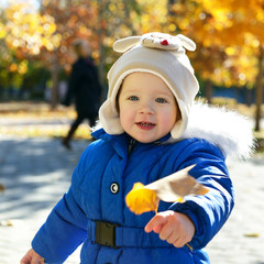 Portrait of cute toddler child playing with leaves in autumn par