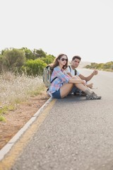 Couple hitchhiking on countryside road