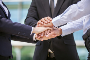 Closeup of business team holding hands together.