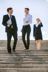 Three happy business people walking together outside.