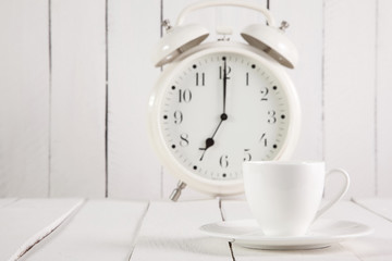 Cup of coffee and alarm clock on wooden table