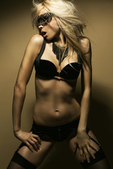 Beautiful, sexy blond woman in black underwear and mask