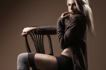 Beautiful blond wearing cardigan and stockings on the chair