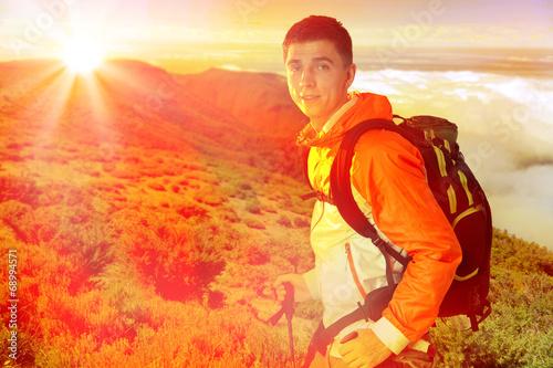 Leinwandbild Motiv wanderer mit rücksack in einem berglandschaft