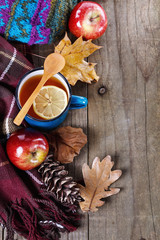 Warm clothing and lemon tea over rustic wooden background