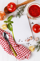 Cooking concept. Recipe book and ingredients for cooking tomato