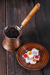 Turkish coffee and Turkish Delight over dark wooden background