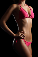 Perfect fitness body wearing a pink bikini on black
