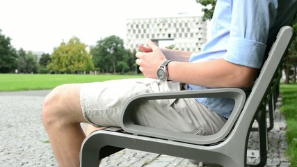 man sitting in the park on bench - pavement - park