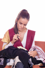 girl with scissors sewing textile