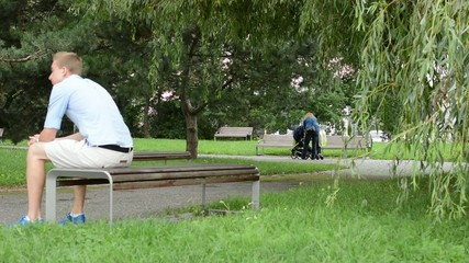 man sitting in the park on bench - woman with child in pram
