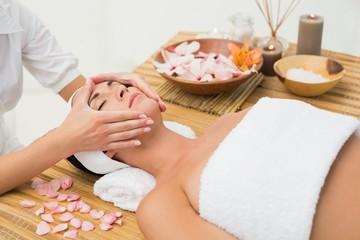 Peaceful brunette enjoying a face massage