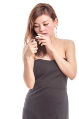 Chinese woman in black dress lighting a cigarette