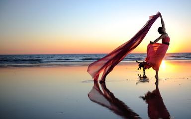 Frau im Roten Kleid am Strand im Sonnenuntergang