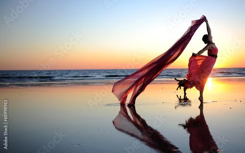 canvas print picture Frau im Roten Kleid am Strand im Sonnenuntergang