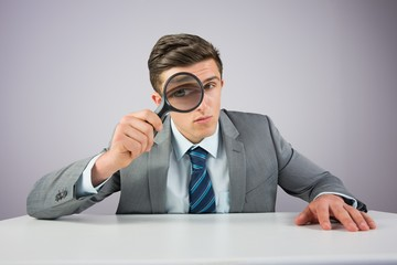 Businessman sitting at desk with magnifying glass