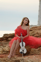 Woman in red dress holds violin at sea shore