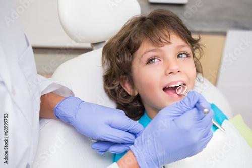 Leinwandbild Motiv Pediatric dentist examining a little boys teeth