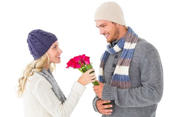 Attractive man in winter fashion offering roses to girlfriend