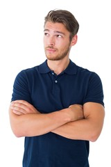 Handsome young man thinking with arms crossed