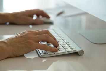 Man working behind his desktop computer.