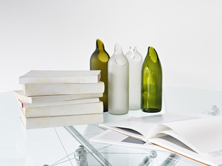 close up of pile of books and glass bottles on the table