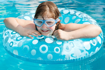 girl in swim goggle on swimming circle
