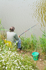 fisherman catches a fish from riverbank