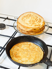 fried pancake and stack of prepared pancakes