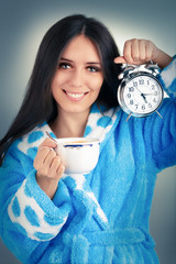 Young Woman in Bathrobe Holding a Clock and a Cup of Coffee