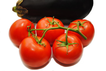 Fresh Tomatoes with an Eggplant in the Background