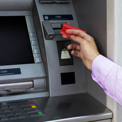 Businessman's hand put credit card at the ATM