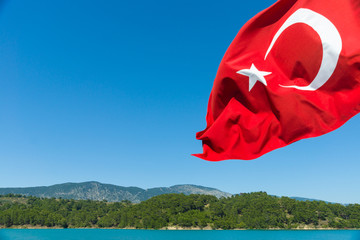 Turkish flag on a background of sky and water.