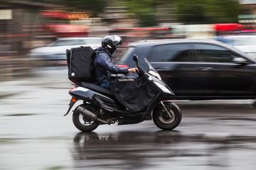Motorroller auf nasser Fahrbahn