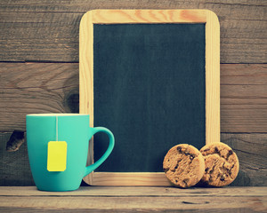Cup of tea, cookies and small blackboard in retro style