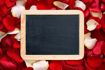 Blackboard in wooden frame on background of rose petals