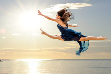 Girl doing artistic jump at sunset