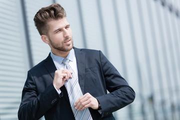 Junger Geschäftsmann bindet Krawatte