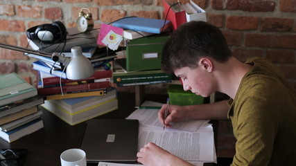 Student reading notes and drinking coffee in desk