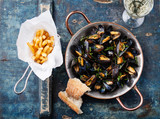 Mussels in copper cooking dish and french fries on blue backgrou