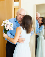 Senior man came to woman with  flowers