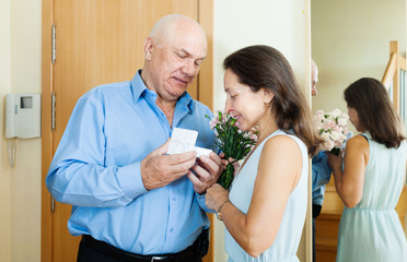 Senior man came to mature woman with gift