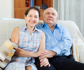Happy mature couple sitting   together in home