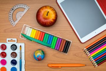 School supplies on wooden school desk from above