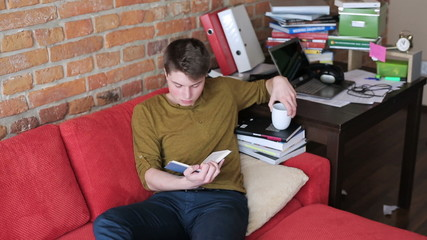 Young man reading book and drinking beverage on red sofa