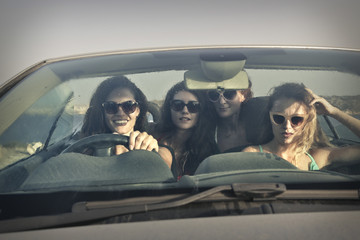 four girls driving a car