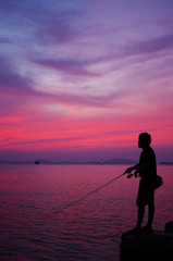 Silhouette of fishing man beside the sea