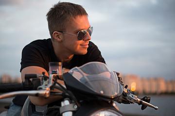 Romantic portrait handsome biker man on a sunset near lake